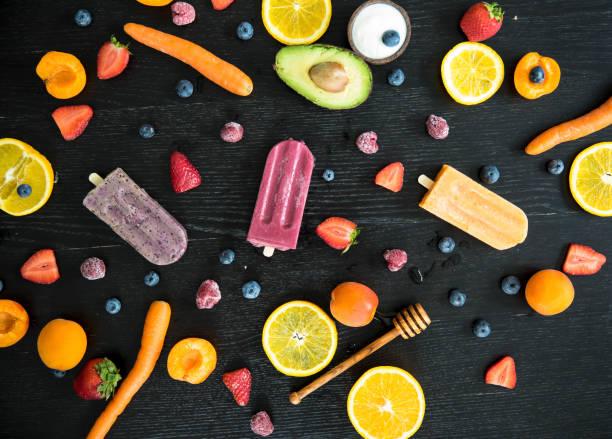 Three various sugar-free popsicles, fruits and vegetables on black wood:スマホ壁紙(壁紙.com)