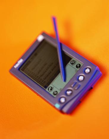 Gel Effect Lighting「Palmtop computer and stylus against orange background, close-up」:スマホ壁紙(18)