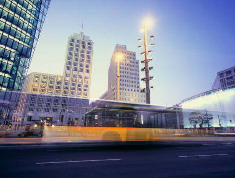 Public Transportation「Potsdammer Platz with office buildings and yellow bus passing in front (motion blurred).」:スマホ壁紙(19)