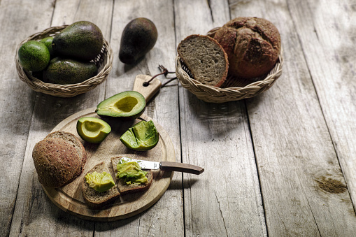 Bun - Bread「Fresh ripe avocado cut in half with fresh flesh spread onto wholewheat organic brown bread, on a wooden cutting board on an old wooden table, with a bowl of ripe and unripe avocados and bread in a basket in the background.」:スマホ壁紙(0)