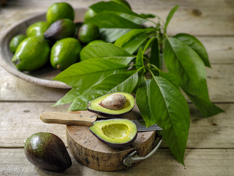 Avocado「Fresh ripe avocado cut in half on a wooden cutting board on an old wooden table, with a bowl of ripe and unripe avocados in the background.」:スマホ壁紙(3)
