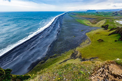 Dyrholaey「The view from the top of the tourist lookout at Dyrholaey near Vik, Southern Iceland. The black sand beach extends for miles into the distance and green pasture and farmland is seen in the background」:スマホ壁紙(9)