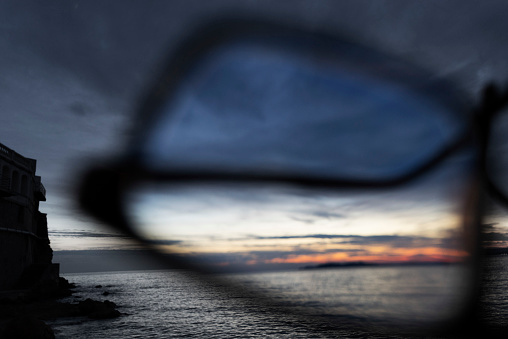 Eyesight「Series of images of black rimmed glasses against rich darkened sky and strong sunlight highlighted over the sea」:スマホ壁紙(0)