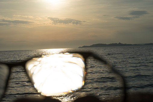 Eyesight「Series of images of black rimmed glasses against rich darkened sky and strong sunlight highlighted over the sea」:スマホ壁紙(4)