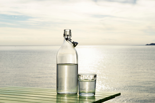 Seascape「Series of images with a bottle and glass of water with setting sun and sea in background」:スマホ壁紙(11)