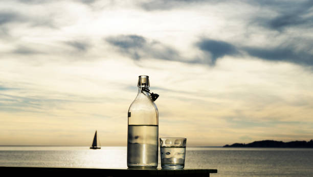 Series of images with a bottle and glass of water with setting sun and sea in background:スマホ壁紙(壁紙.com)