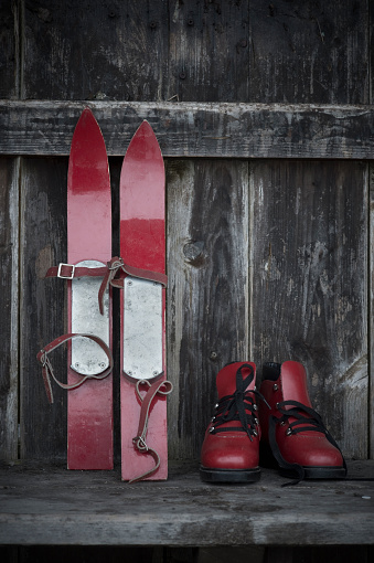 スキーブーツ「Pair of red childrens ski and red ski boots on old wooden bench」:スマホ壁紙(5)