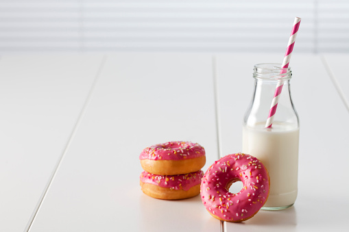 ドーナツ「Glass bottle of milk and three doughnuts with pink icing on white ground」:スマホ壁紙(4)