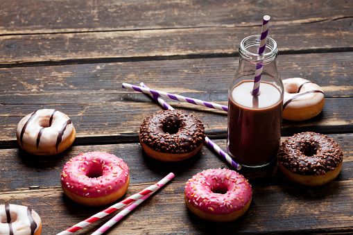 Donut「Glass bottle cocoa, drinking straws and doughnuts with different icings on dark wood」:スマホ壁紙(7)