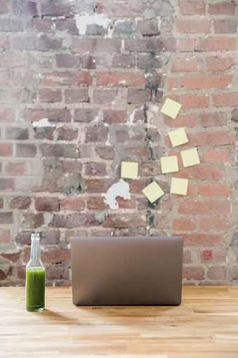 Small Office「Glass bottle of green smoothie and laptop on wooden tabletop in a loft」:スマホ壁紙(4)