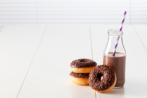 Icing「Glass bottle of cocoa and three doughnuts with chocolate icing on white ground」:スマホ壁紙(11)