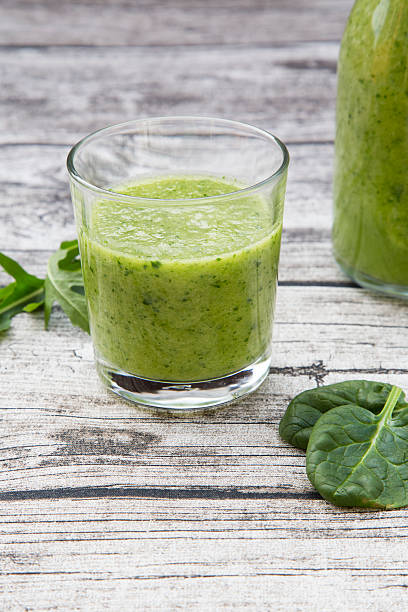 Glass bottle and glass of green smoothie made of spinach, rocket salad, apple, orange, banana and cucumber, on grey wooden table:スマホ壁紙(壁紙.com)