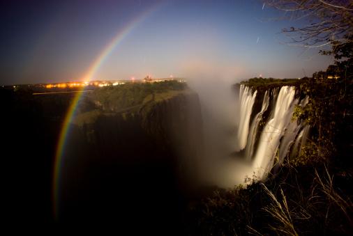 虹「Night scene of moon rainbow over deep gorge with waterfall on right, town lights on left, star streaks in sky,  Victoria Falls, Livingstone, South Africa」:スマホ壁紙(6)