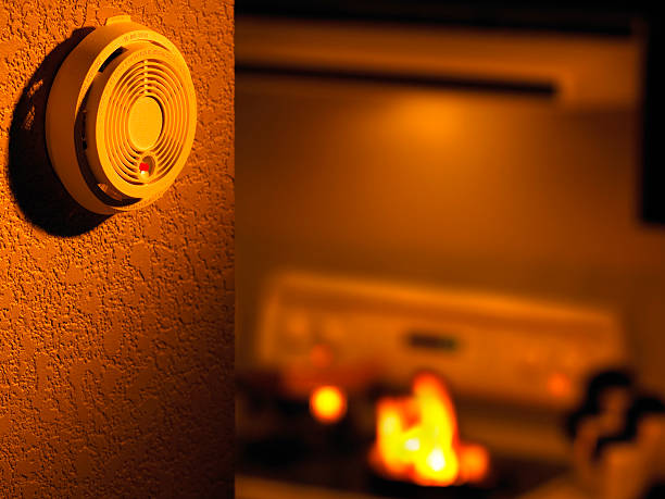 An off-centered view of a smoke detector, a small kitchen fire is in the background:スマホ壁紙(壁紙.com)