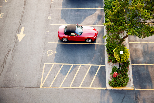 オーシャンシティー「Red sports car in a parking lot seen from above」:スマホ壁紙(1)