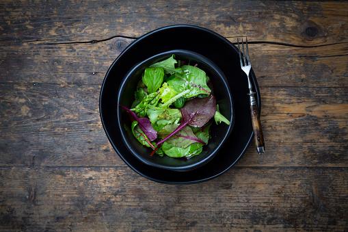 Organic「Bowl of organic mixed salad on dark wood」:スマホ壁紙(6)