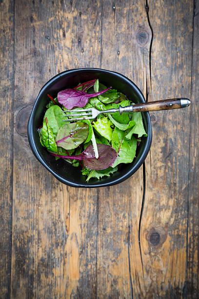 Bowl of organic mixed salad on dark wood:スマホ壁紙(壁紙.com)