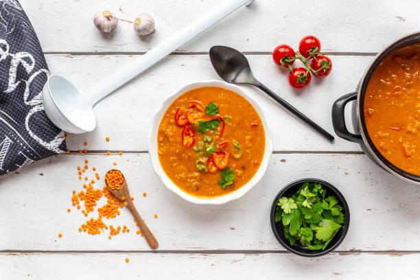 Bowl and pot of garnished red lentil soup and ingredients on white wood:スマホ壁紙(壁紙.com)