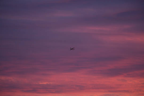An aeroplane takes off into deep red clouds at sunset:スマホ壁紙(壁紙.com)
