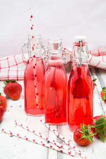 ソーダ「Three glass bottles of homemade strawberry lemonade and strawberries on white wood」:スマホ壁紙(10)