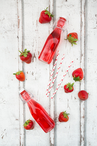 ソーダ「Three glass bottles of homemade strawberry lemonade and strawberries on white wood」:スマホ壁紙(12)