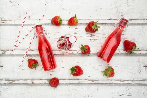 ソーダ「Three glass bottles of homemade strawberry lemonade and strawberries on white wood」:スマホ壁紙(11)