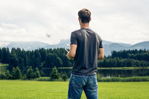 コントロール「Germany, Bavaria, Pfronten, young man flying his drone at lakeside」:スマホ壁紙(1)