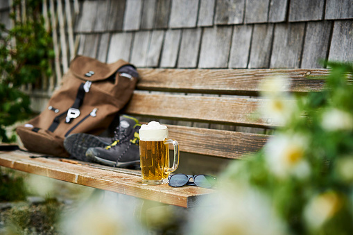 Bavaria「Germany, Bavaria, glass of beer, backpack, sunglasses and hiking shoes on wooden bench」:スマホ壁紙(1)