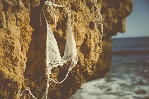 水着「Bikini top hanging on a rock on the beach」:スマホ壁紙(16)