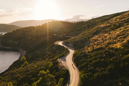 逆光「Italy, Elba Island, biker on coastal road against the sun, aerial view with drone」:スマホ壁紙(14)