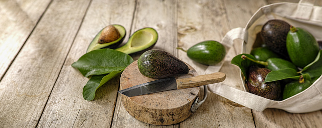 The Knife「Fresh market avocado on a wooden cutting board next to a knife with more avocados in a cotton reusable shopping bag to the right of the image.」:スマホ壁紙(1)