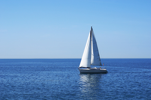 Yacht「A sailboat on blue calm waters」:スマホ壁紙(12)