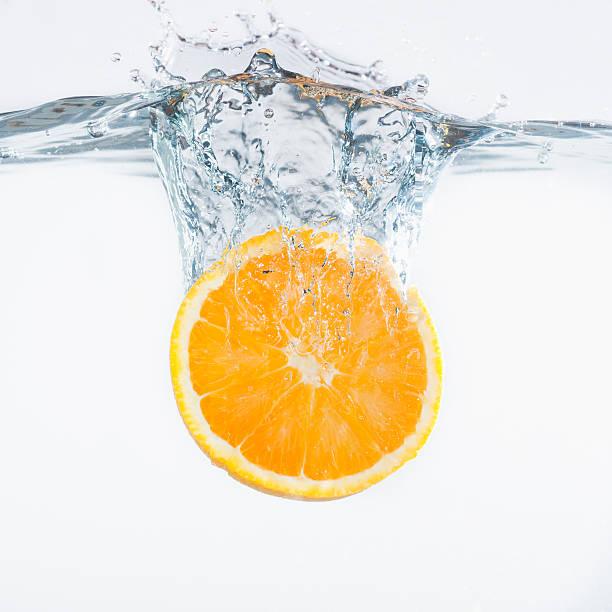 Orange splashing into water, studio shot:スマホ壁紙(壁紙.com)