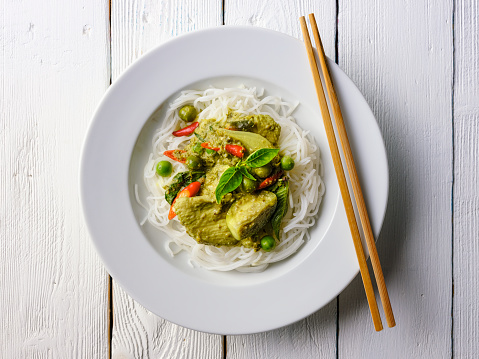 Rice Noodles「Famous internationally renowned Thai green coconut curry 'Gaeng Keow Wan Gai', with chicken on top of fresh Thai rice noodles, in a dish, along with traditional chopsticks, set on an old worn white wooden background.」:スマホ壁紙(9)