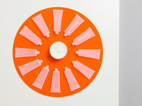 時計「Empty frosted cosmetics bottles in a circle on an orange perspex circle」:スマホ壁紙(15)