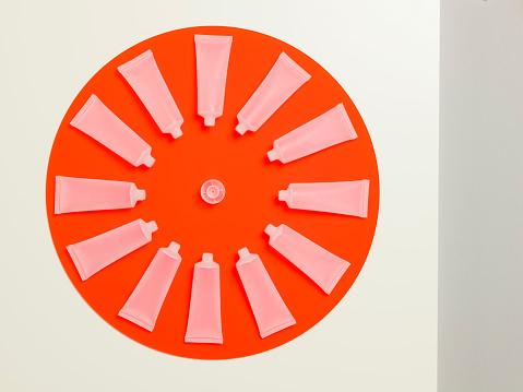 時計「Empty frosted cosmetics bottles in a circle on an orange perspex circle」:スマホ壁紙(16)