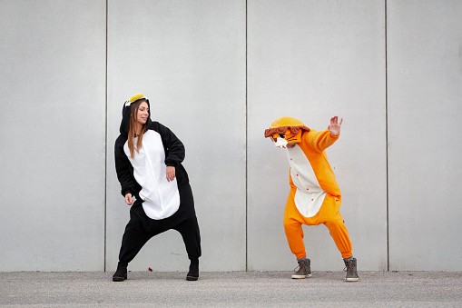 Caucasian Ethnicity「Two women in penguin and lion costume in front of concrete wall」:スマホ壁紙(6)