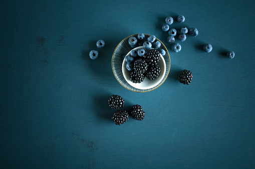 Blueberry「Blueberries and blackberries in bowls on blue ground」:スマホ壁紙(1)