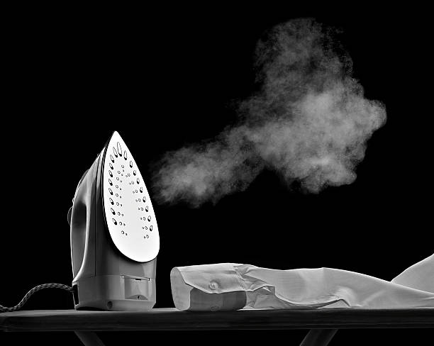 Steaming flat iron and shirt sleeve in front of black background:スマホ壁紙(壁紙.com)