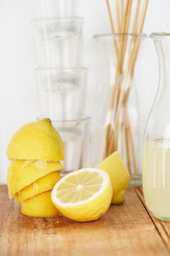 Halved「Carafe of lemon juice, glasses, sliced and squeezed lemons on wood」:スマホ壁紙(4)