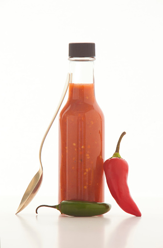 Chili Sauce「Homemade hot sauce in a small bottle with jalapeno peppers and a spoon around it」:スマホ壁紙(6)