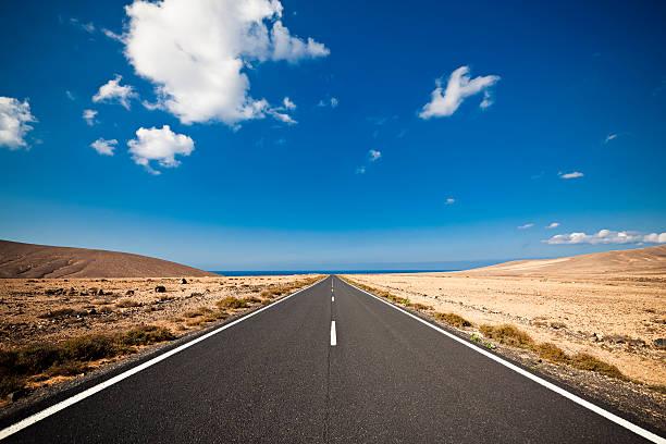 Long road in the desert heading into a blue sky:スマホ壁紙(壁紙.com)