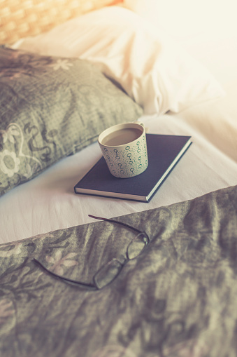 趣味・暮らし「Book, reading glasses and cup of white coffee on bed」:スマホ壁紙(0)