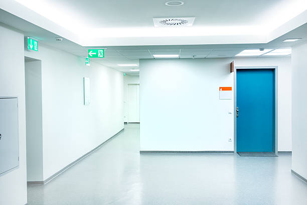Empty white Hospital corridor with a blue door:スマホ壁紙(壁紙.com)