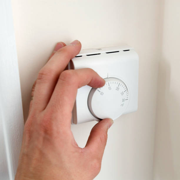 Person adjusting thermostat:ニュース(壁紙.com)