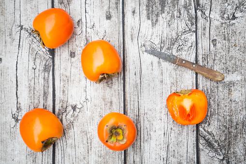 柿「Whole and sliced kaki persimmons and a kitchen knife on wood」:スマホ壁紙(1)