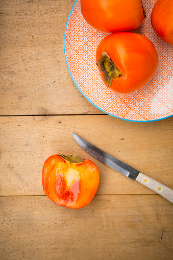 柿「Whole and sliced kaki persimmons and a kitchen knife on wood」:スマホ壁紙(3)