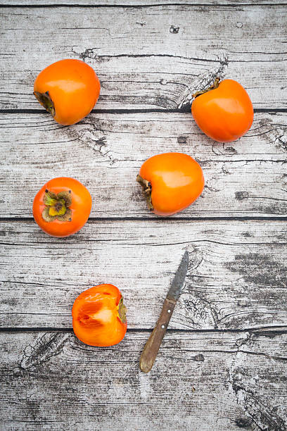 Whole and sliced kaki persimmons and a kitchen knife on wood:スマホ壁紙(壁紙.com)