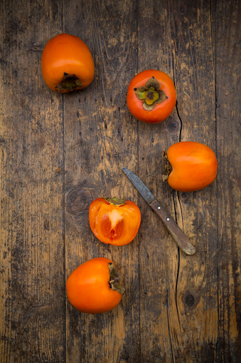 柿「Whole and sliced kaki persimmons and a kitchen knife on wood」:スマホ壁紙(7)