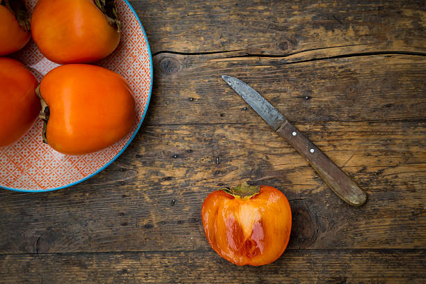Whole and sliced kaki persimmons and a kitchen knife:スマホ壁紙(壁紙.com)